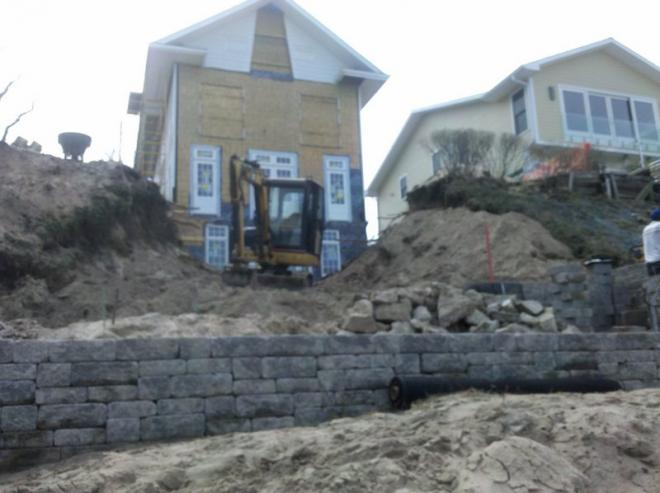 landscapers installing retain wall in Grand Beach