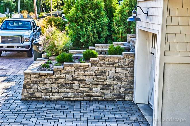 retaining wall for driveway with flowers and bushes